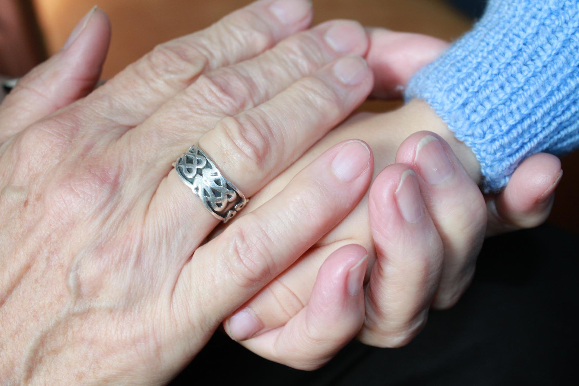 mano anziano che tiene mano bambino